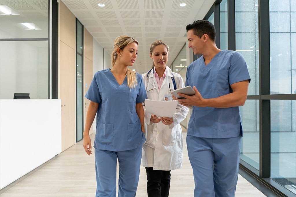 doctor and nurse walk down corridor with tablet